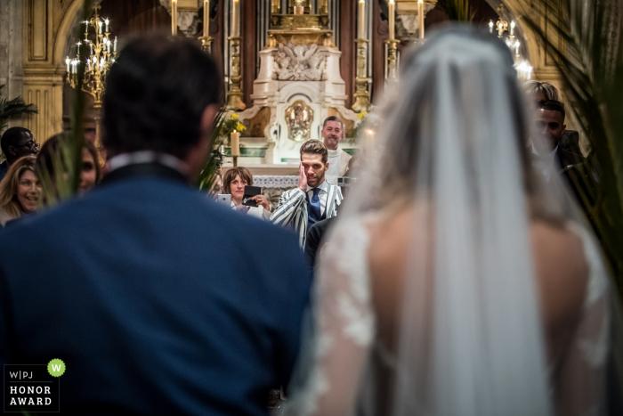 Montpellier, France Photographe de mariage dans une église - le marié réagit en voyant sa fiancée marcher dans l'allée avec son père