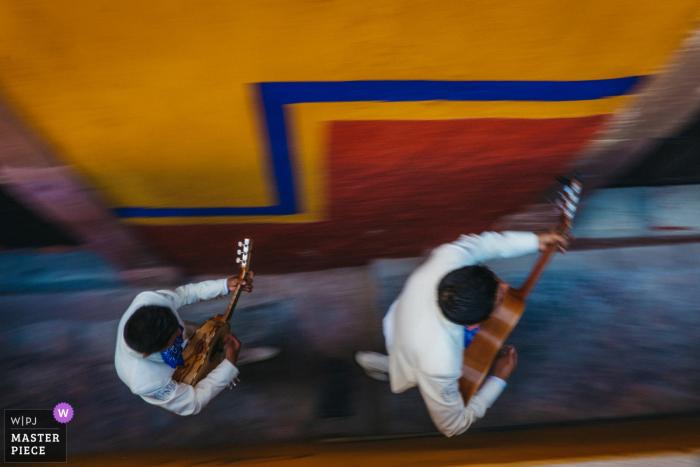 Hombres de San Miguel, México tocando guitarras mientras caminan por la acera