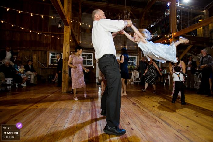 Le marié se balance autour de petite fille sur la piste de danse à la grange à Harvest Moon Pond, Poynette,