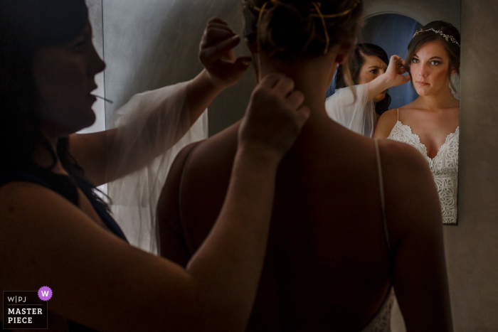 Santorini, novia de Grecia recibiendo ayuda para prepararse para la ceremonia de boda
