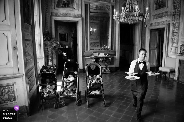 Villa Botta Adorno, hombre de Torre d'Isola con platos de comida junto a cochecitos en la boda