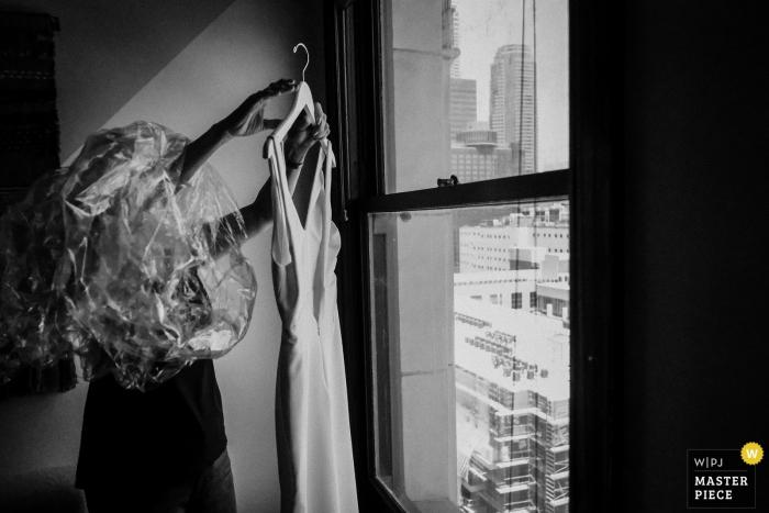La novia de los angeles sostiene su vestido delante de una ventana antes de la boda