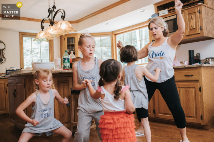 Photo of the bride warming up before the reception by dancing in the kitchen with kids at her house