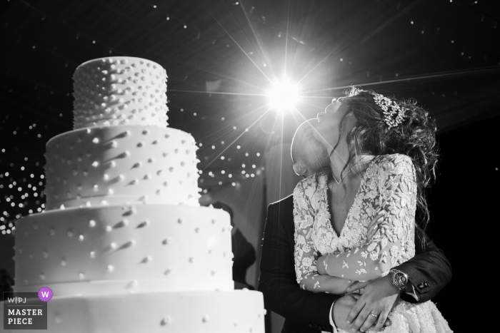 Photo of bride and groom hugging in front of the wedding cake at Como Lake, Italy