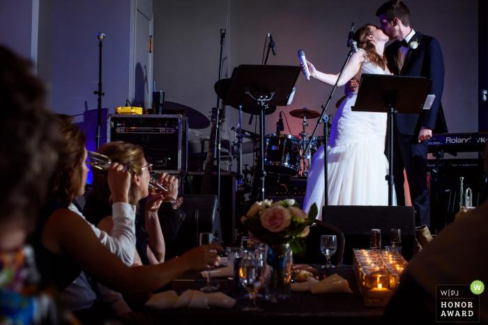 Omaha, Nebraska Wedding Photographer - the bride and groom kiss on stage after a toast