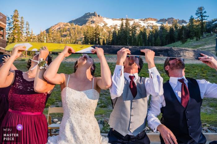 Bruids partijschoten naast een ski samen buiten bij de huwelijksontvangst bij Meer Tahoe, Californië