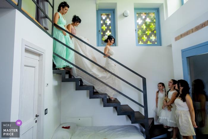 Bruid loopt de trap af met haar bruidsmeisjes in Italië