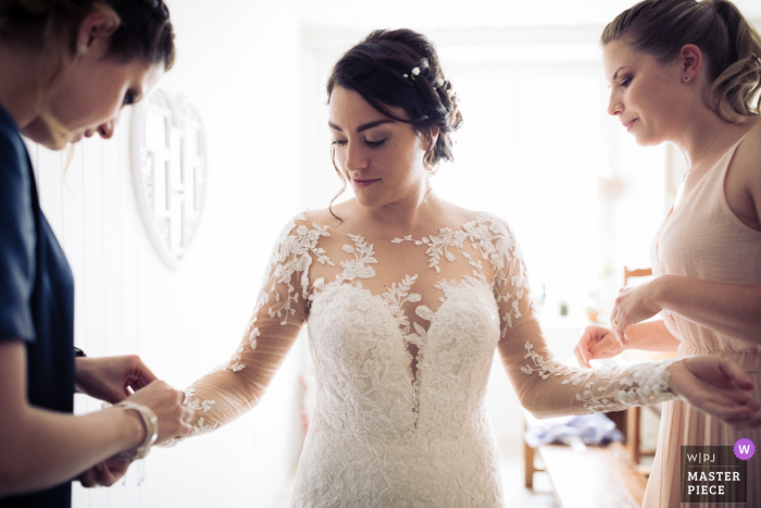 Photo of bride getting help with her dress before the wedding ceremony in Le Locle, Switzerland