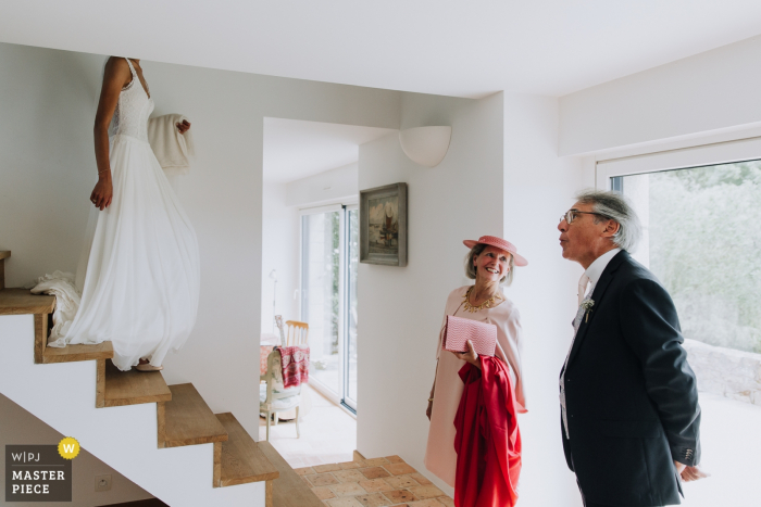 The bride's mother and father wait downstairs as she makes her way from above