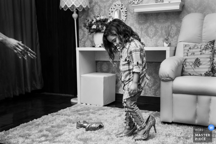 Image of the young flower girl trying on high heel shoes before the wedding ceremony in Salão Marcos Soares Sete Lagoas- MG