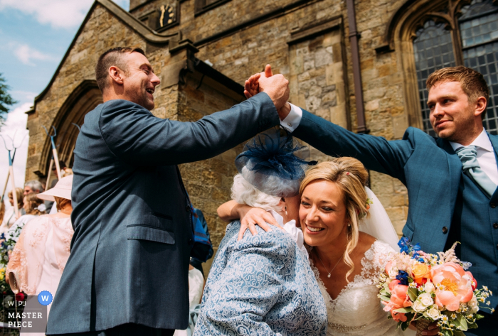 Outdoor photo of groom and guest shaking hands while bride hugs woman after the wedding in Ribble valley, Uk