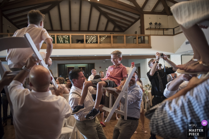 Guests lift up kids in chairs at the wedding reception in Moreaga, California