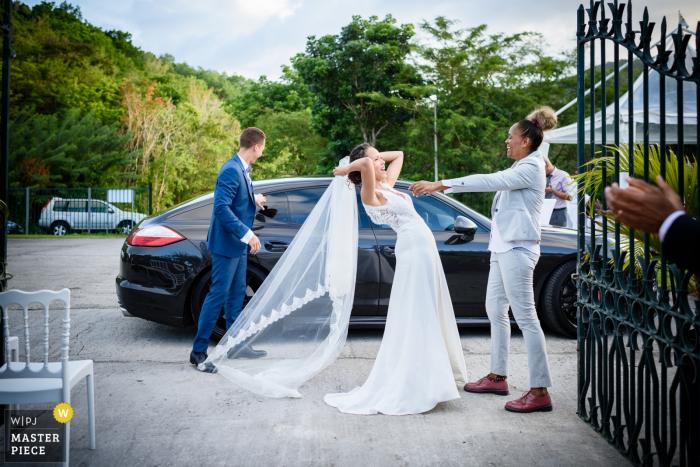 Photo extérieure de la mariée avant de monter dans la voiture après le mariage aux Trois Ilets, Martinique