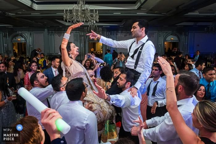 Gäste heben Braut und Bräutigam hoch, während sie auf der Hochzeitsfeier im The Henry Hotel Dearborn tanzen