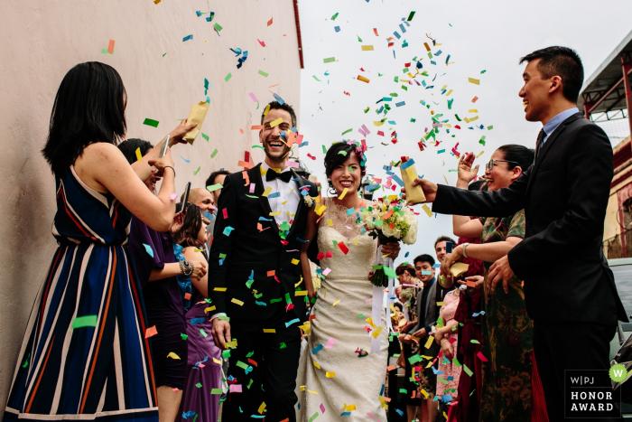 Oaxaca City, Oaxaca, Mexico bride and groom under a rainbow colored shower of confetti