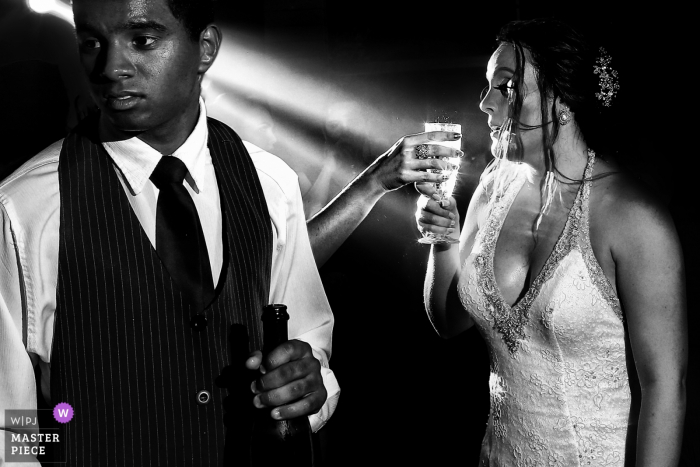 Bride and groom holding their drinks at the wedding reception in Goiânia
