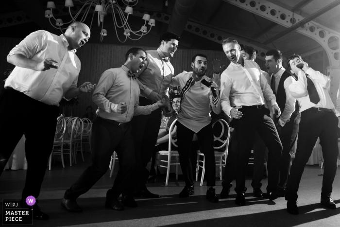 Novios y padrinos de boda bailan y cantan en la recepción de la boda en Bucarest