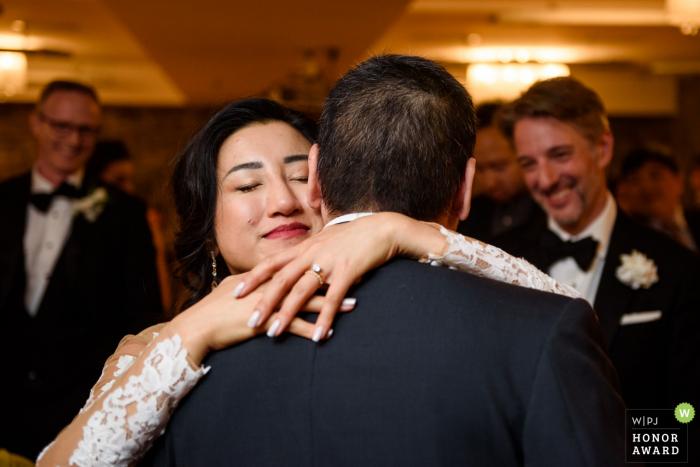 Montréal Québec Braut umarmt ihren Vater, während der Bräutigam lächelt