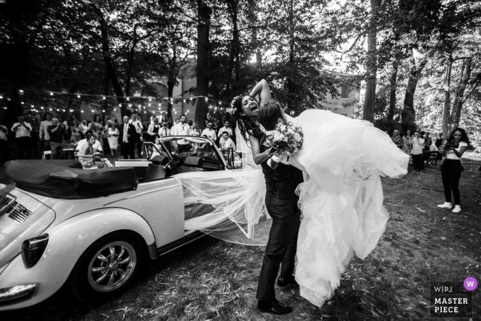 Modena Bräutigam hebt die Braut in die Luft draußen am Hochzeitsempfang beim Verlassen des konvertierbaren VW-Käfers.