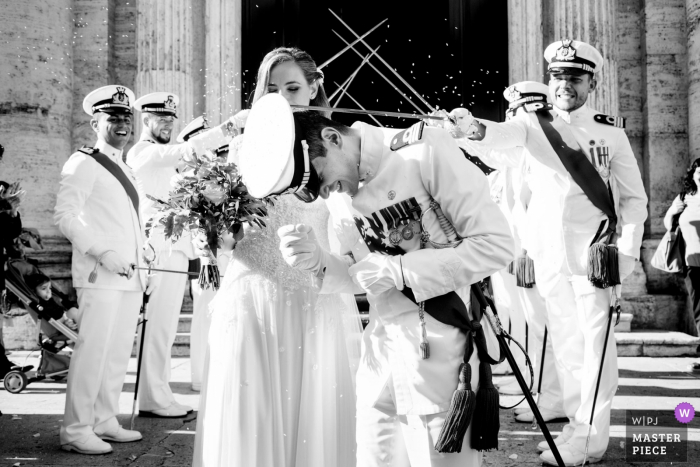 Traditional groom's military hat falling down with help from swords - Santa Maria in Vallicella, Rome, Italy