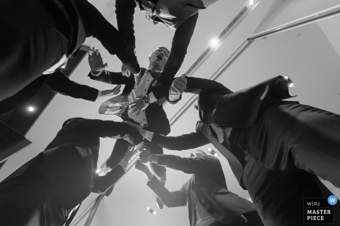 Groomsmen throw the groom into the air at the wedding reception in Taiwan
