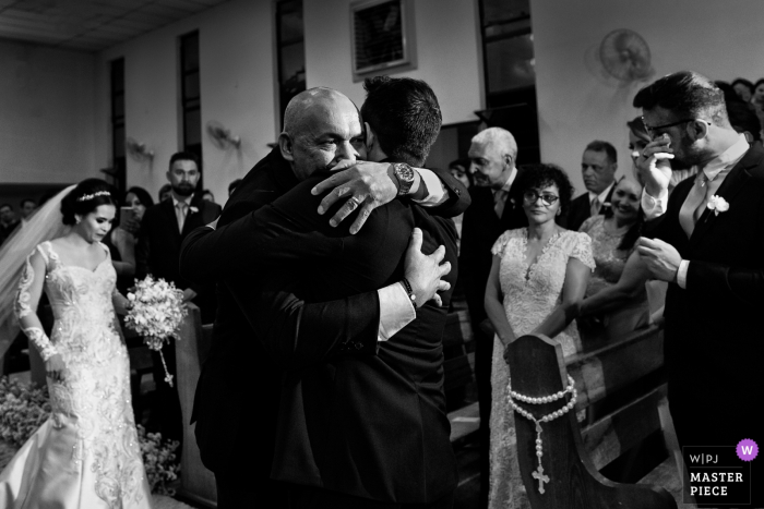Groom hugs the brides father during the wedding ceremony in Goiânia