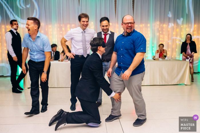 Les invités slovènes rient pendant que le marié a les yeux bandés lors de la réception de mariage