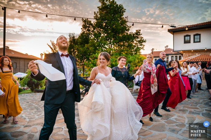 La novia, el novio y los invitados bailan en una fila afuera en esta foto de un fotógrafo de bodas de Burgas, Bulgaria.