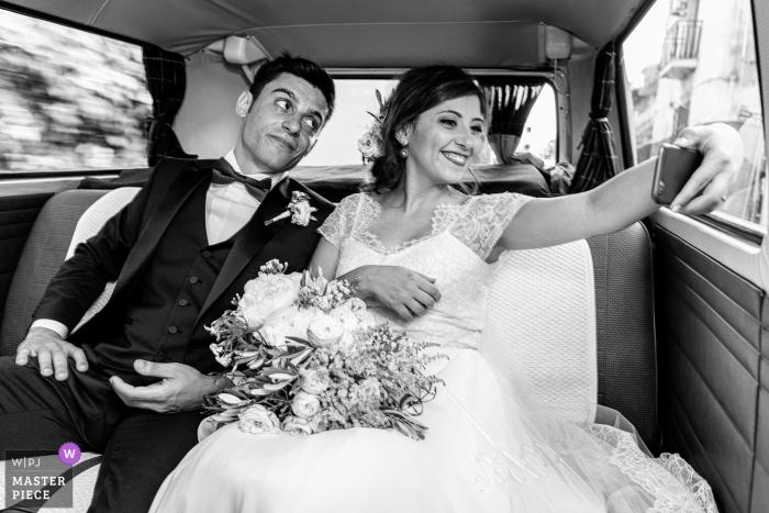Schwarzweiss-Foto der Braut, die ein selfie mit ihrem Bräutigam in einem Fahrzeug von einem Sizilien-Hochzeitsfotografen macht.