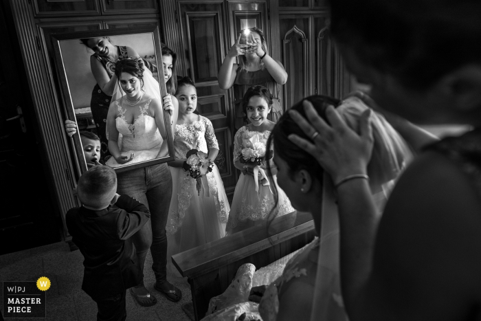 A mirror is held up for the bride as members of the bridal party watch her and take photos in this black and white photo by a Calabria wedding photographer.