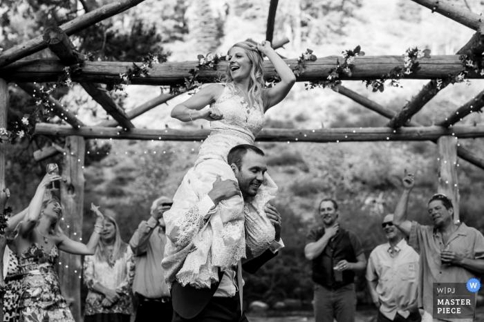 Photo noir et blanc prise à Truckee, en Californie, de la mariée assise sur les épaules du marié par un photographe de mariage à Lake Tahoe.