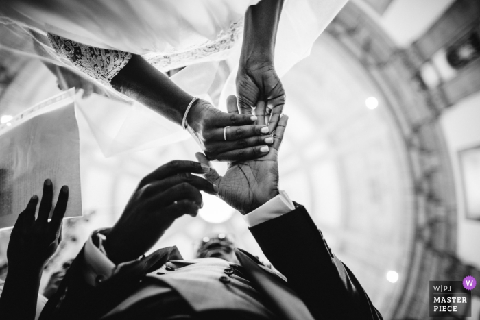 The bride puts the ring on her groom in low angle this black and white photo by a Portugal wedding photographer.