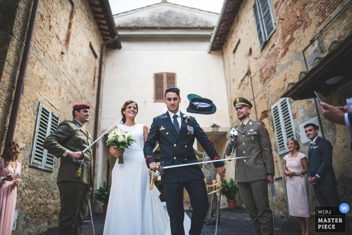 Siena bruiloft foto van de bruidegom krijgt zijn hoed verwijderd van zijn hoofd door een zwaard tijdens militaire bruiloft.