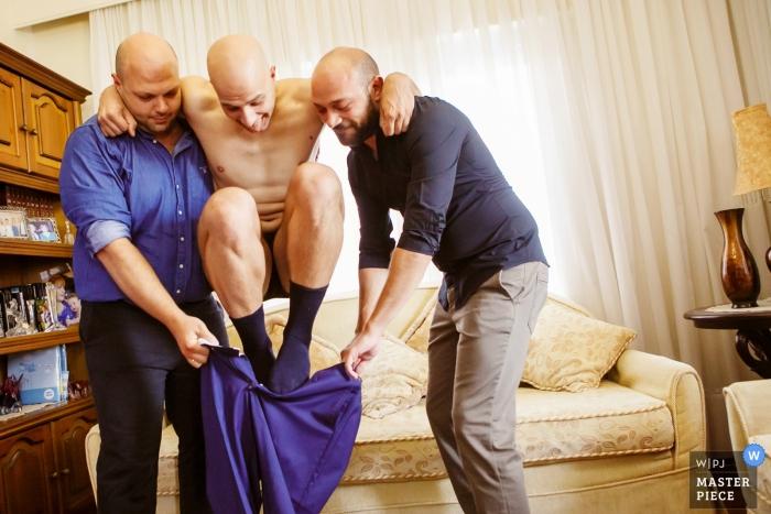 Veria trouwfoto van twee groomsmen die bruidegom helpen in zijn broek te stoppen.