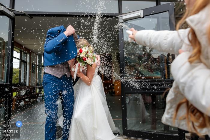 Braut und Bräutigam heirateten gerade, mit Reis bombardiert zu werden