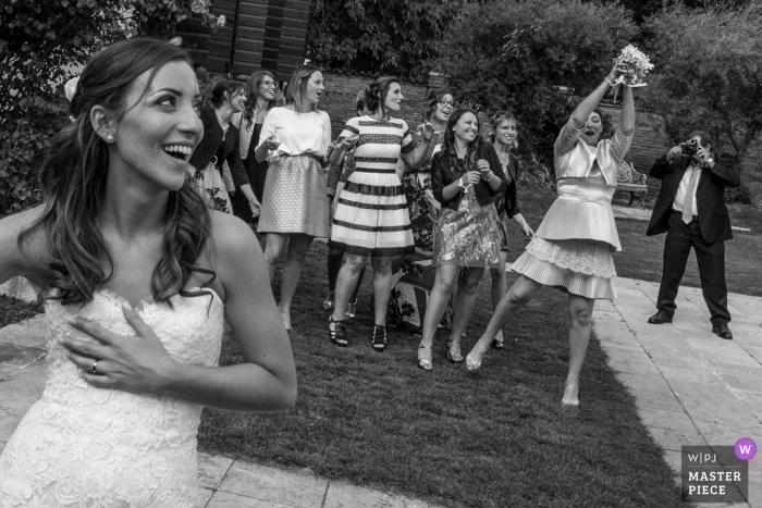 Mantova Wedding Photojournalist | samotna pani łapie bukiet panny młodej na tej recepcji