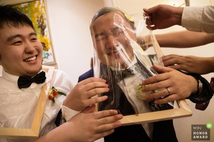 Trauzeugen, die Spaß haben, dem Bräutigam während der traditionellen Türspiele in China zu helfen