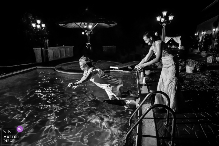 Athens Wedding Photojournalist | the bride pushes a woman into the pool at this outdoor night wedding reception party