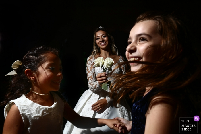 Goiânia Wedding Photojournalist | the bride enjoys time with dancing flower girls