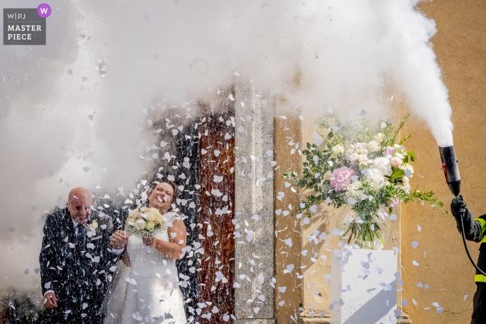 Lecco Wedding Fotojournalist | de bruid en bruidegom verlaten de kerk en worden bespoten door een brandweerman met behulp van een brandblusser