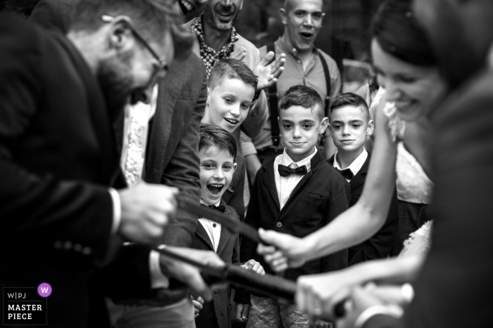 Cherasco Wedding Photojournalist   Black and white photo of boys watching the bride and groom saw a log together