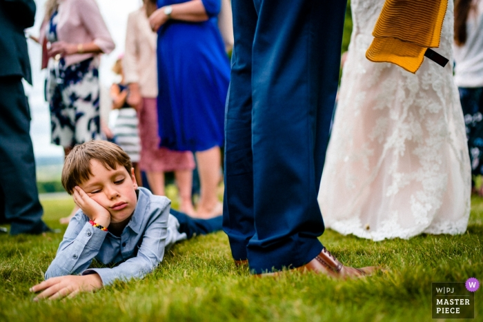 Boughton Monchelsea Place, UK wedding photograph of a bored boy lying on the reception grass.