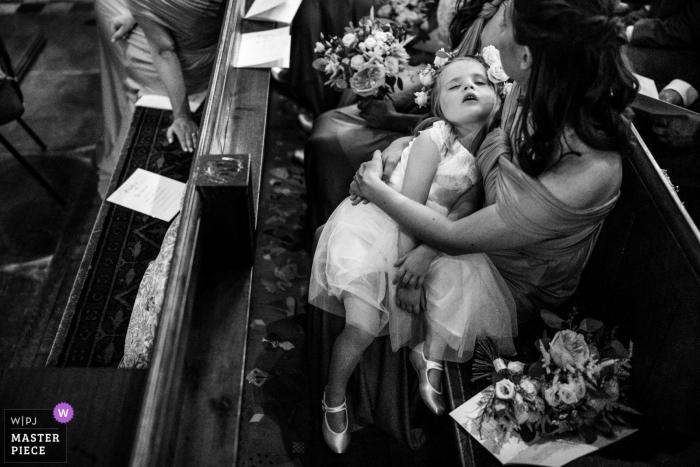 Ticehurst, East Sussex, fotografia ślubna Wielkiej Brytanii śpiącej dziewczynki w kościelnych ławkach podczas ceremonii.