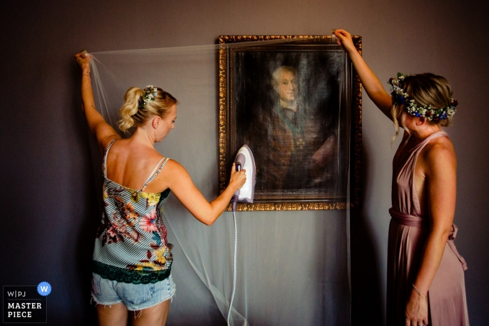 Hesse Wedding Photojournalist | the bride steams her veil while getting ready in Germany