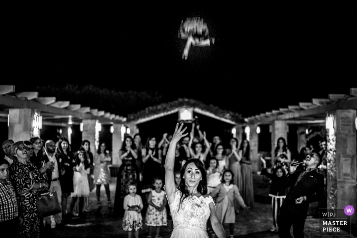 wedding photography in puglia | bride tossing bouquet of flowers at night