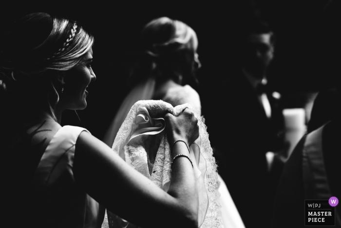 Bridesmaid carries bride's dress at Church, Bromsgrove