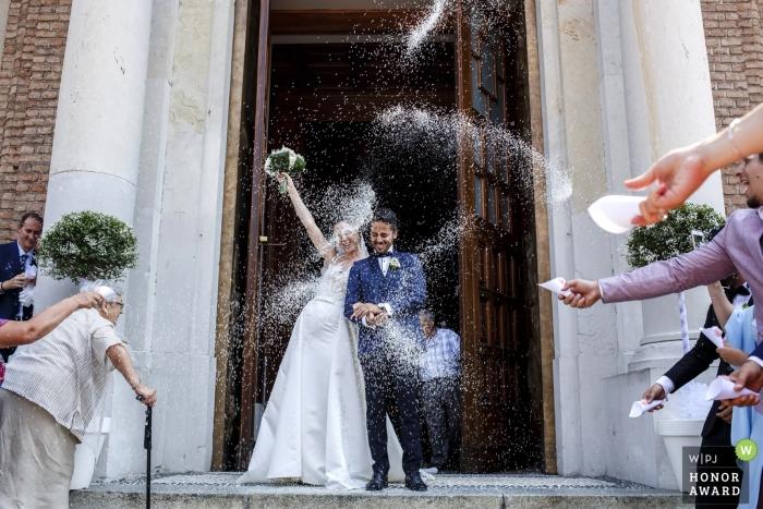 Italia invitados tiran arroz a los novios después de la ceremonia de boda de milano