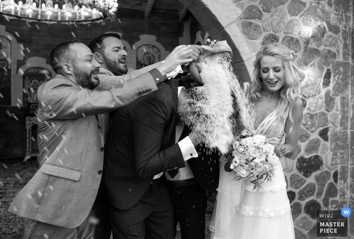 Attica Wedding Photojournalist | Athens groom gets showered with a heavy dose of rice by two friends after the wedding ceremony