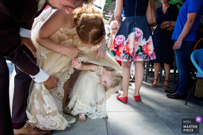 Enkhuizen Het Station wedding photograph of young flower girl hiding under the bride's dress.
