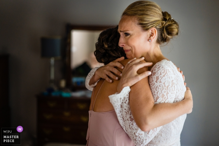 Wedding photo in Boston of the bride receiving a hug from a friend - client home photography